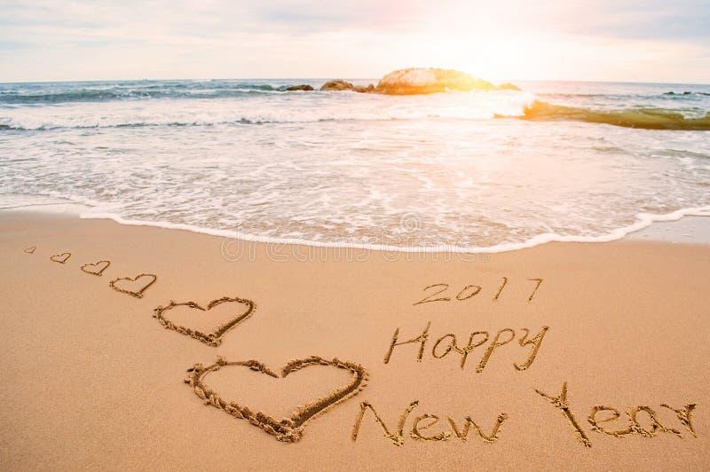 Skriv 2017 lyckliga nya år på stranden med hjärtor royaltyfria foton