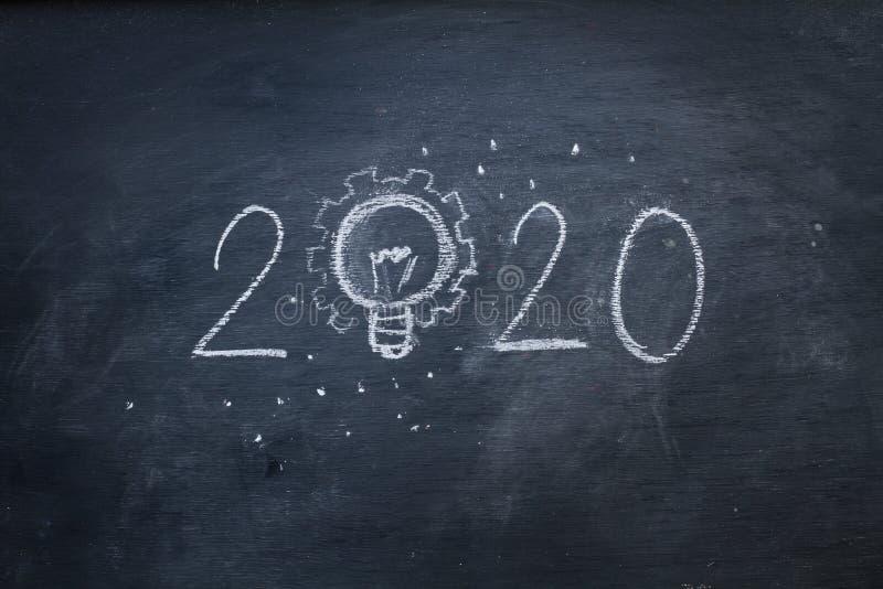 Skriv 2020 med ljus idé på svarta tavlan royaltyfria foton