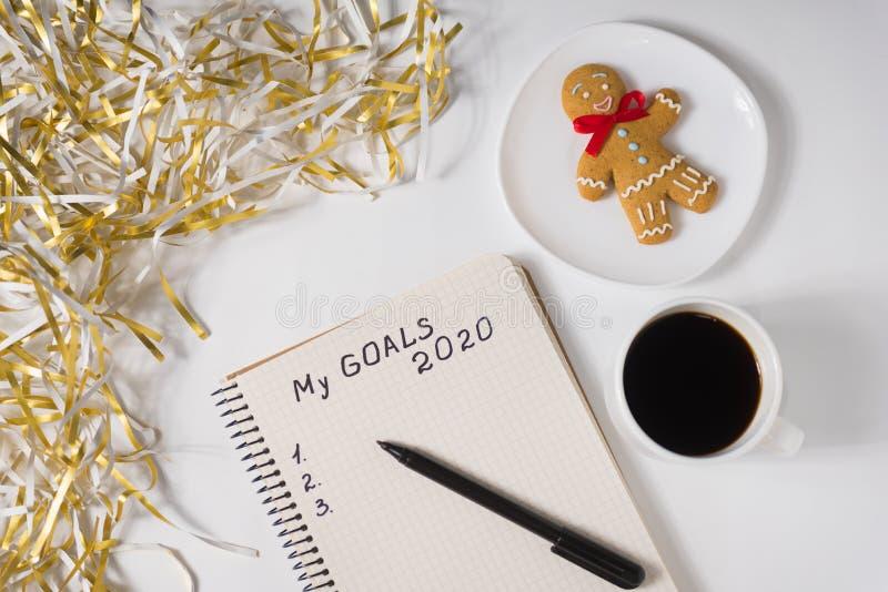 Skriv mina mål 2020 i en bärbar dator, penna Massa av kaffe, glasbröd och tinsel Överkant arkivfoto