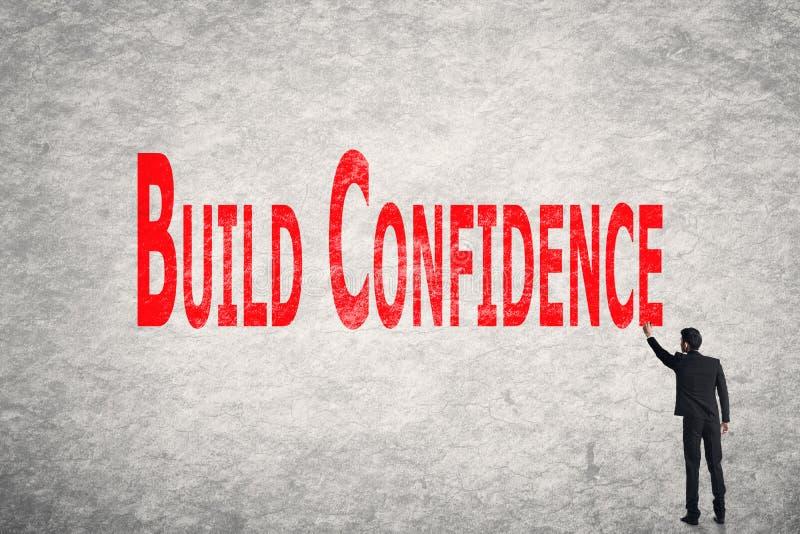 Skriv ord på väggen, byggandeförtroende royaltyfri foto