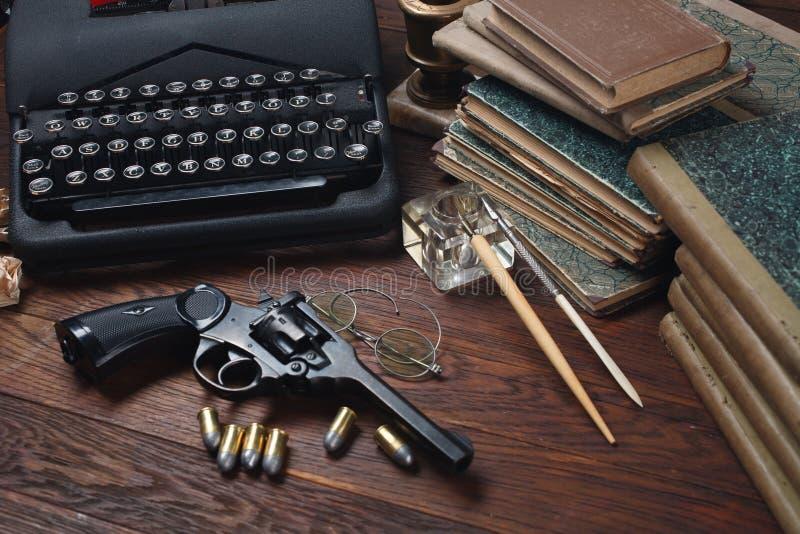 Skriva en brotts- fiktionberättelse - gammalt retro tappningskrivmaskin och revolvervapen med ammunitions, böcker, legitimationsh arkivfoto