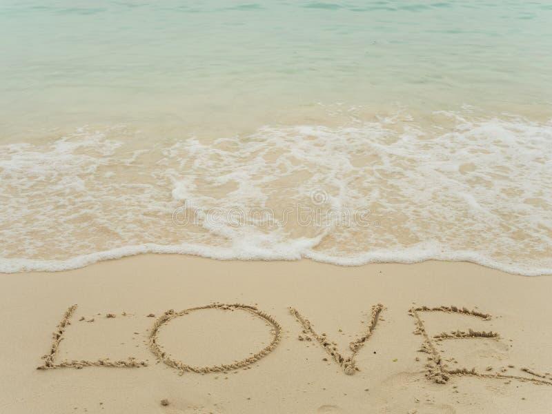 Skriva förälskelse på stranden royaltyfri fotografi
