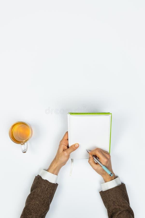 Skriva i en anteckningsbok, bästa sikt royaltyfri bild