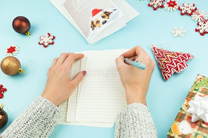 Skriva jul som hälsar bokstaven Bästa sikt av kvinnliga händer med pennan på blå bakgrund med papper, feriestöttor och gåvor, och royaltyfria foton