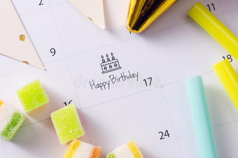 Skriva kakan p? lycklig f?delsedag f?r kalender royaltyfria foton