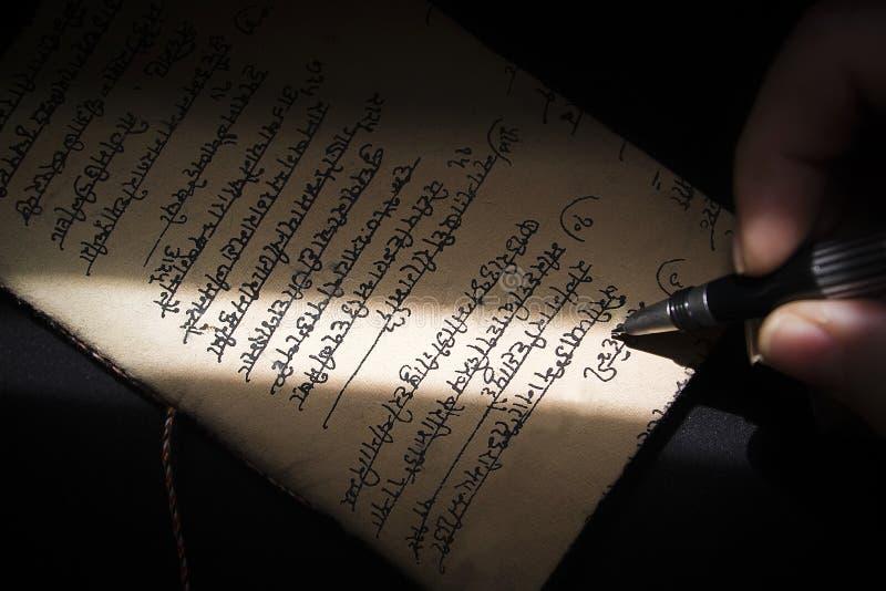 Skriva med en penna på en papyrus arkivfoton