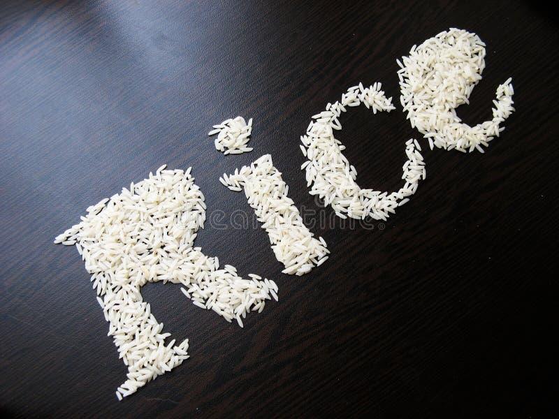 Skriva ordrisen med risfr? p? en tabell med brun tr?bakgrund arkivfoton