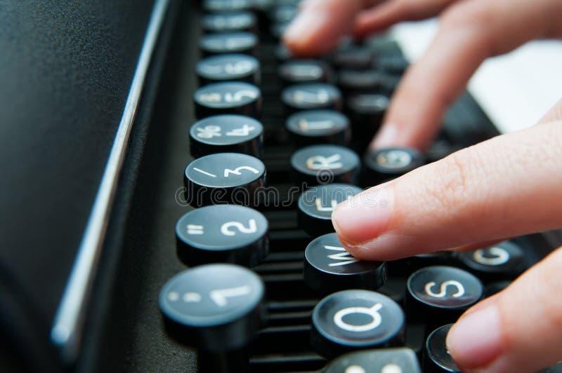 Skriva på ett gammalt tangentbord arkivfoto