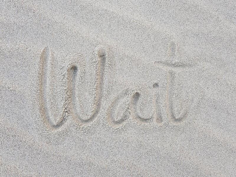 Skriva på sandstranden arkivbild