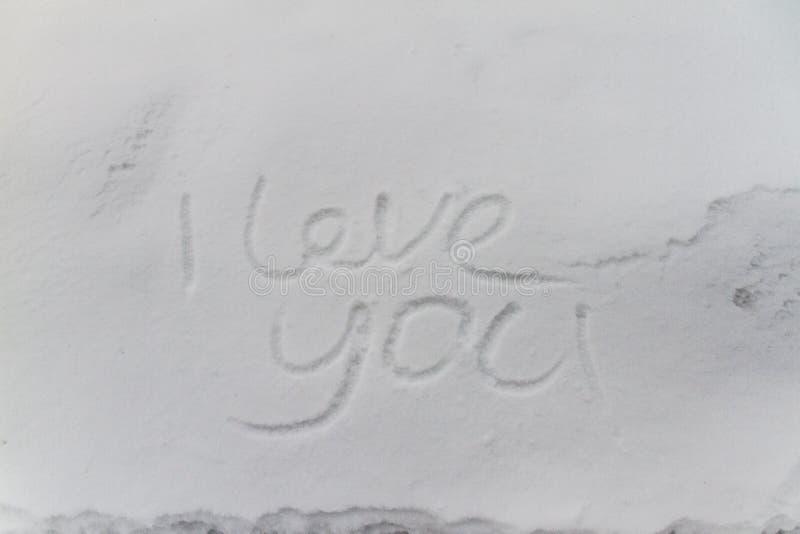 Skriva text ÄLSKA DIG på snön arkivfoto