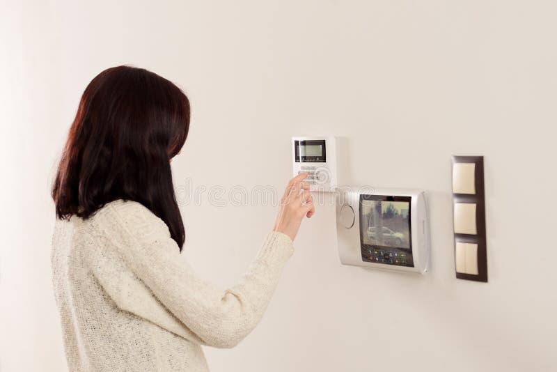 Skrivande in kod för kvinna på tangentbord av larmet för hem- säkerhet fotografering för bildbyråer