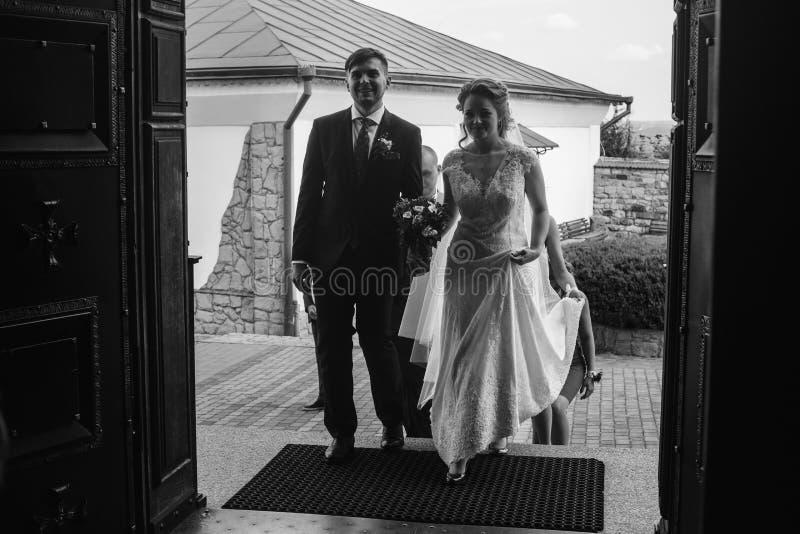 Skrivande in kyrka för lyckliga par, härlig brud i vitt gifta sig D arkivbild