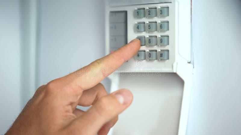 Skrivande in lösenord för man på systemet för hem- säkerhet, röveriskydd, slut upp fotografering för bildbyråer