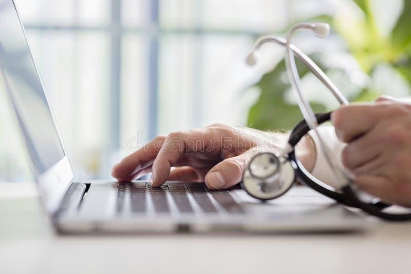 Skrivande in patientanmärkningar för doktor på bärbara datorn i kirurgi arkivbild