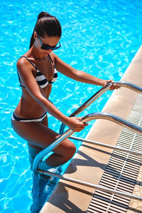 Skrivande in simbassäng för brunett vid trappa fotografering för bildbyråer