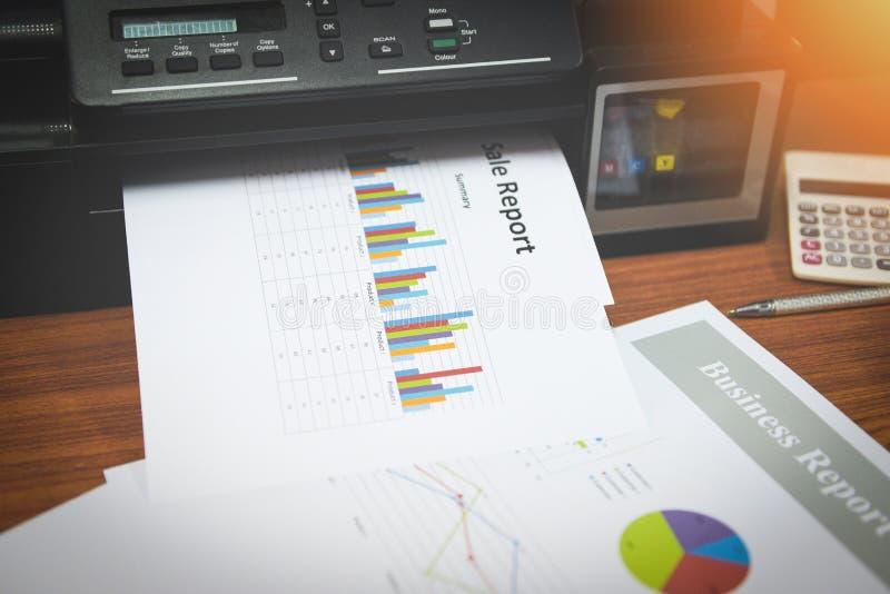 Skrivaren som skrivar ut affärsrapporter försäljning och hög av dokument, anmäler grafdiagrammet på ett tabellkontor royaltyfri fotografi