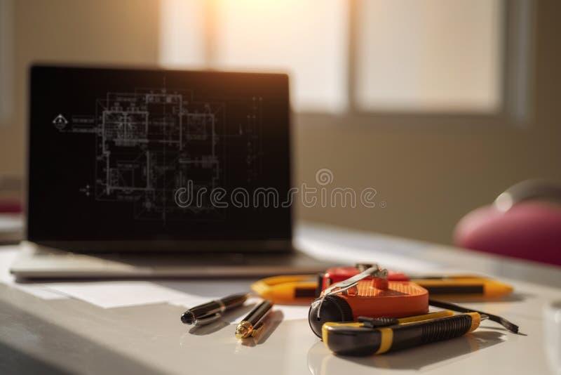 Skrivbord av arkitektteknikern med en ritning på tabellen i kontoret Iscensätta hjälpmedel och konstruktionsbegrepp arkivbilder