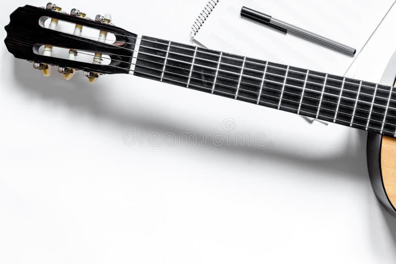 Skrivbord av musikern för låtskrivarearbetsuppsättning med modellen för bästa sikt för bakgrund för gitarr och för papper den vit royaltyfri foto