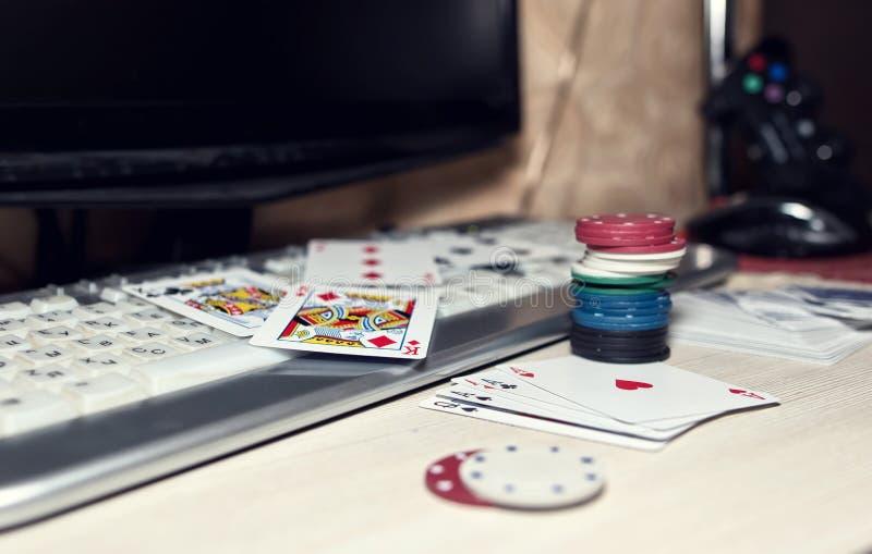 Skrivbord av spelaren i online-kasino med spridda kort och po royaltyfri fotografi