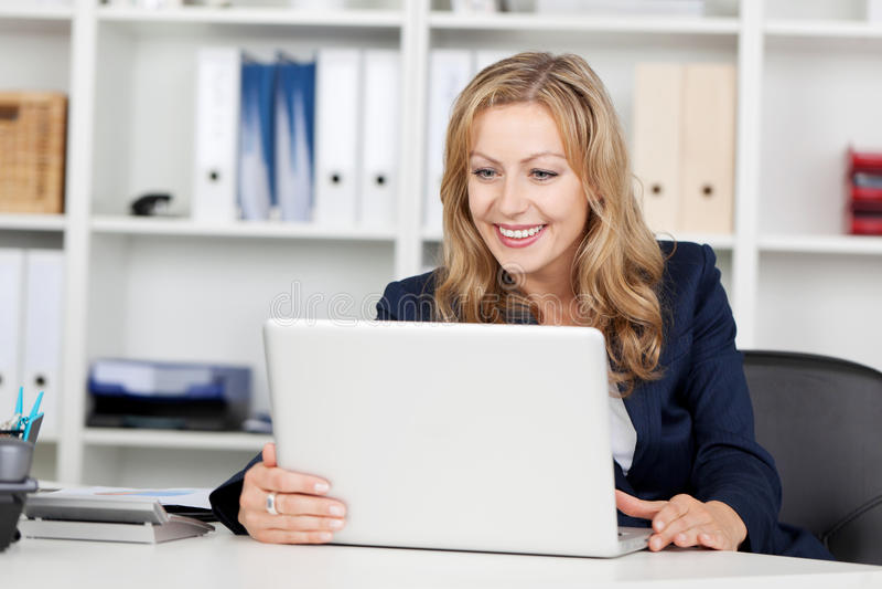 Skrivbord för affärskvinnaUsing Laptop At kontor arkivfoton