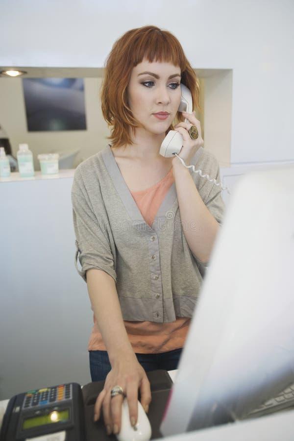Skrivbord för receptionistAnswering Telephone At mottagande arkivfoton