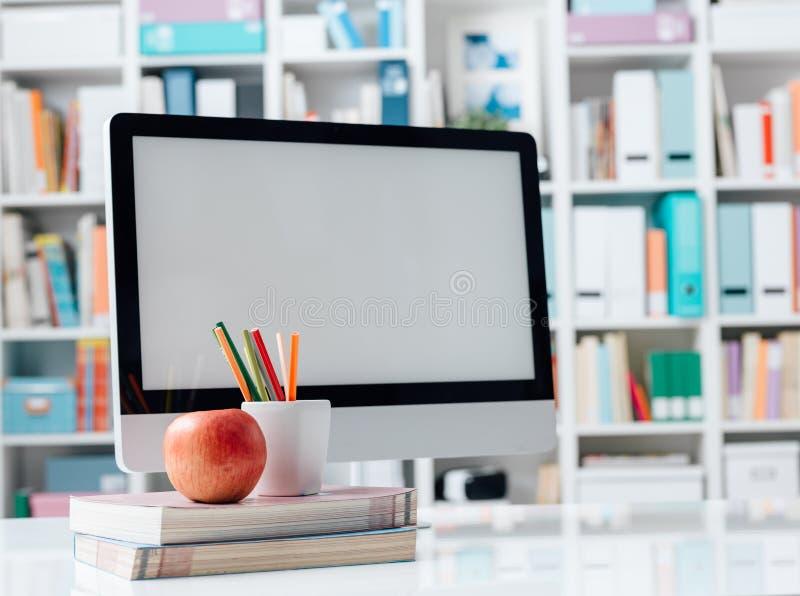 Skrivbord för student` s med datoren och böcker arkivfoton
