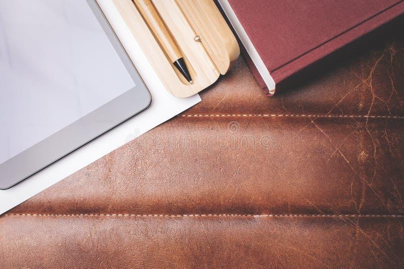 Skrivbord med apparaten och boken royaltyfria foton