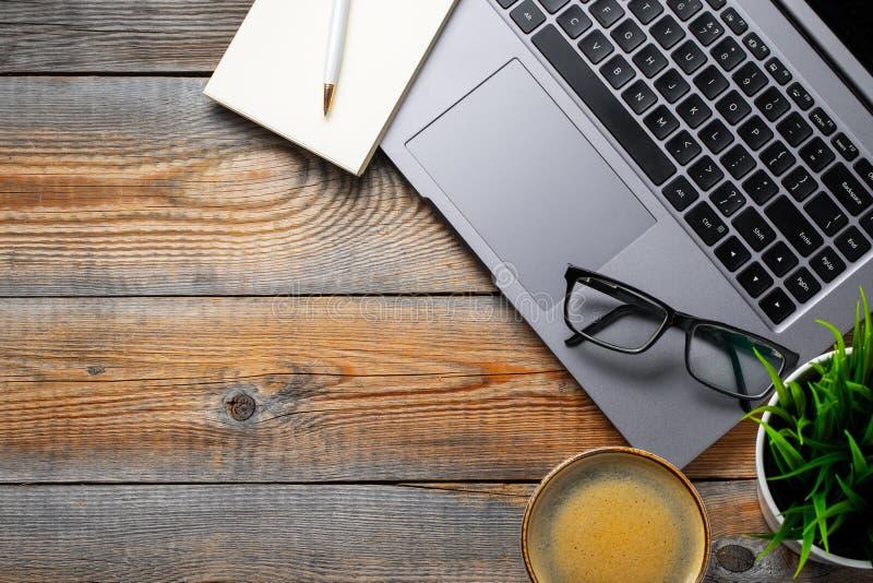 Skrivbord med bärbara datorn, glasögon, notepaden, pennan och en kopp kaffe på en gammal trätabell Bästa sikt med kopieringsutrym arkivfoton