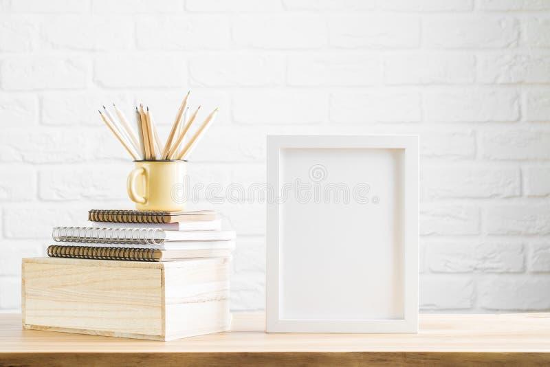 Skrivbord med den tomma ramen och tillförsel royaltyfri fotografi