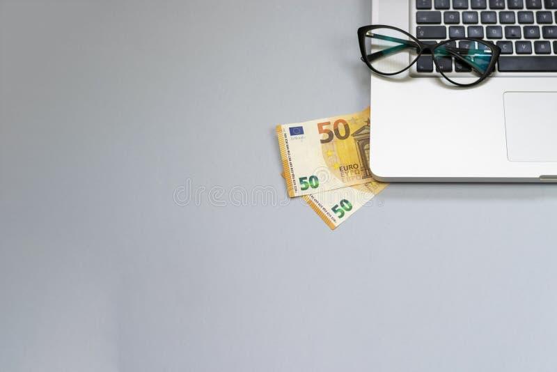Skrivbord med pengar, b?rbar dator, exponeringsglas royaltyfria foton