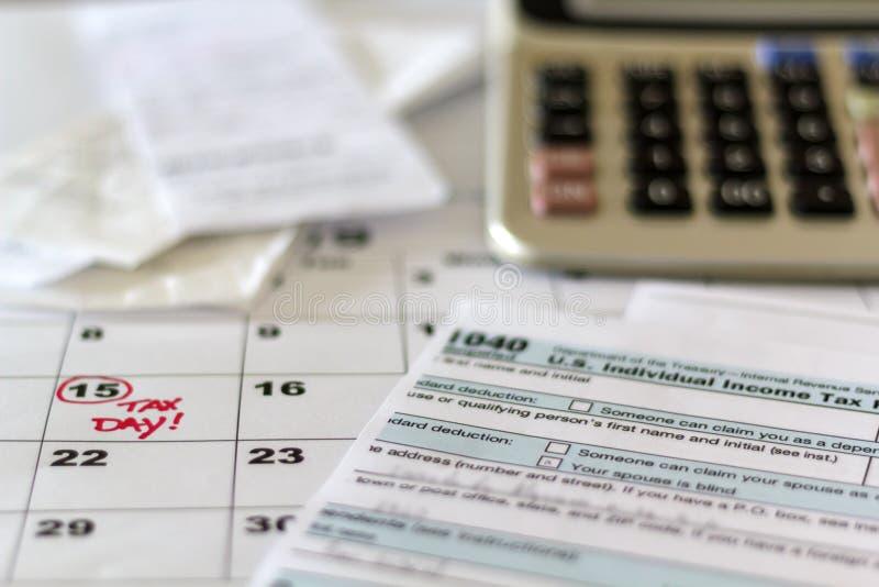 Skrivbord med skattformen, kvitton, räknemaskinen och kalendern Finansiellt skattbegrepp för redovisa arkivfoto