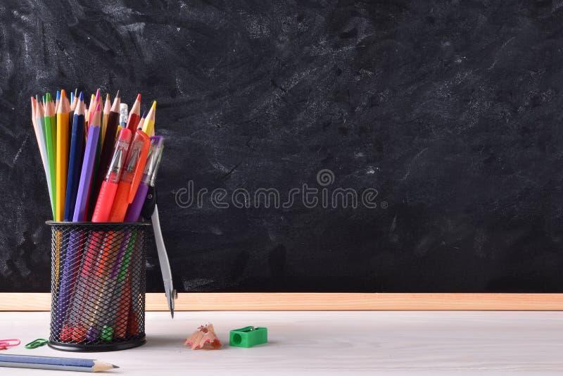 Skrivbord med skolahjälpmedel och högert svart tavlaställe för titel royaltyfri bild