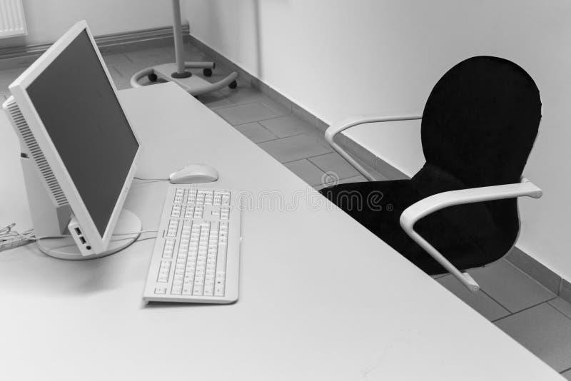 Skrivbord med stol, PCbildskärmen och tangentbordet royaltyfri bild