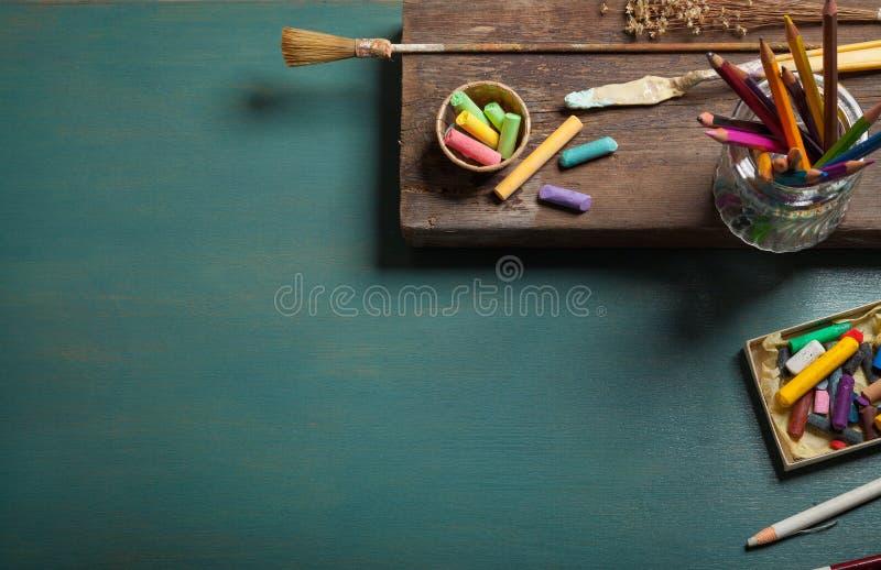 Skrivbordet av en konstnär med massor av brevpapper anmärker på grön träbakgrund royaltyfria bilder