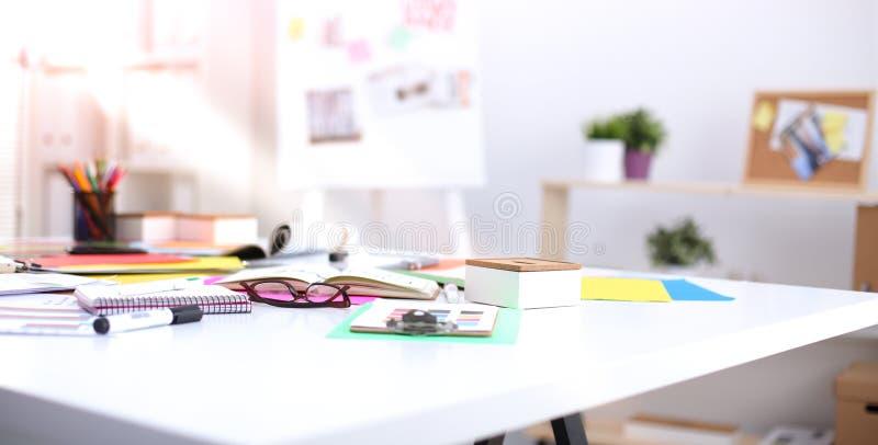 Skrivbordet av en konstnär med massor av brevpapper anmärker Studio som skjutas på träbakgrund arkivbild
