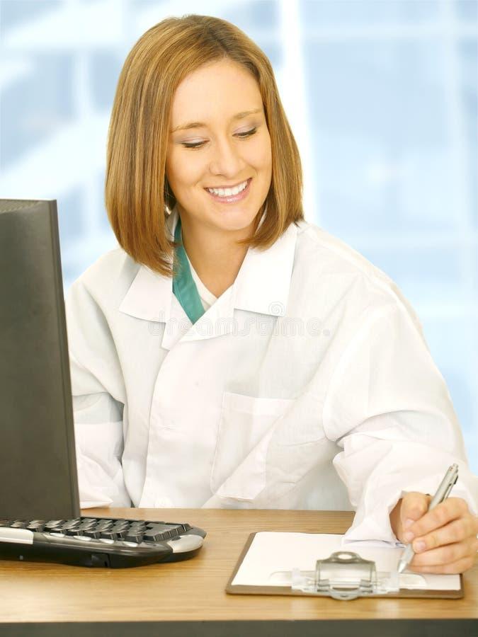 skrivbordet doctor henne kvinnaworking royaltyfri foto