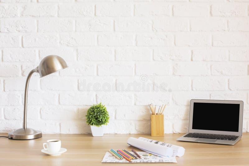 Skrivbordet med bärbara datorn och skissar arkivbild