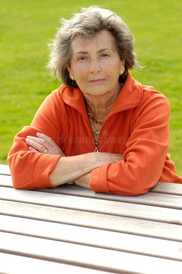 skrivbordpensionärkvinna royaltyfria bilder