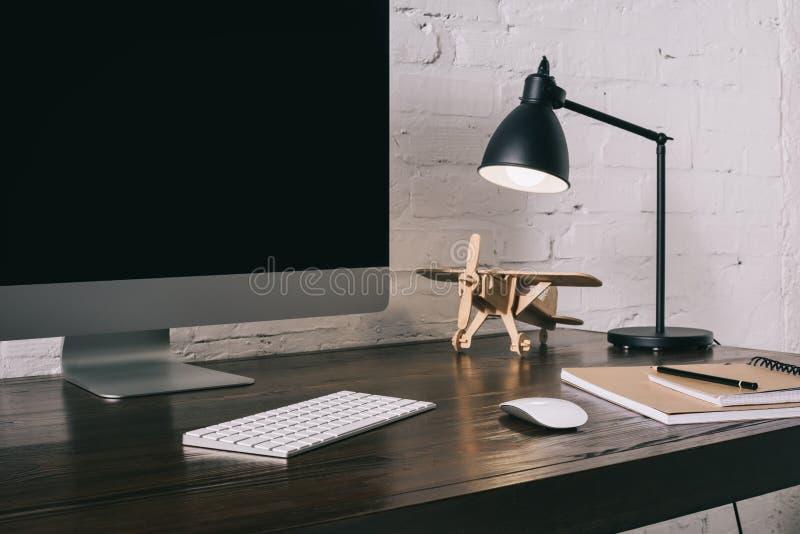 skrivbords- dator med den tomma skärmen och den träplana modellen fotografering för bildbyråer