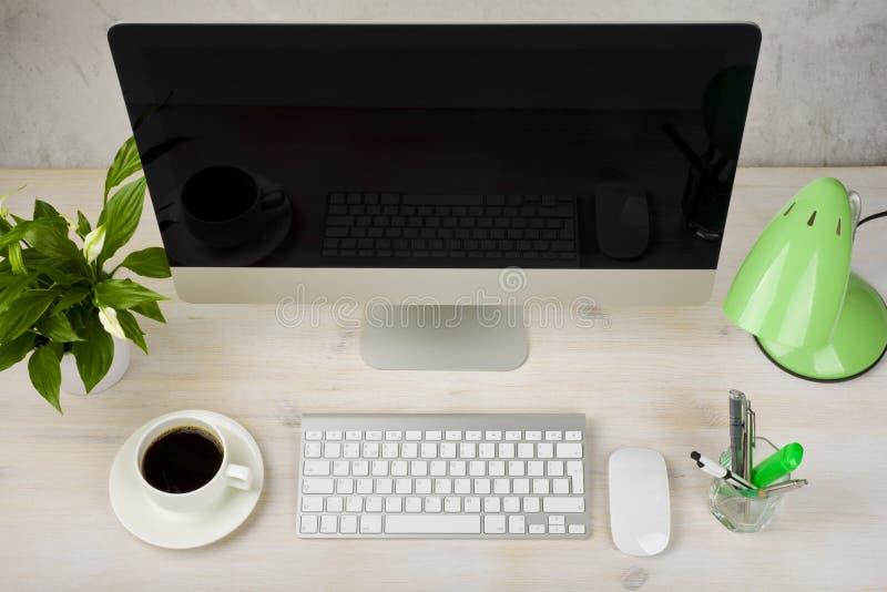 Skrivbords- dator och tillbehör på trätabellen Top beskådar royaltyfri fotografi