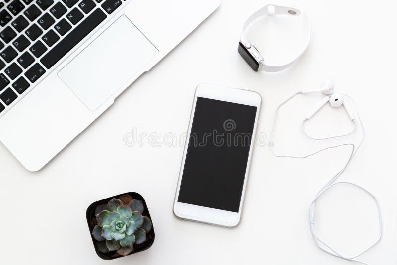 Skrivbords- objekt: bärbar dator suckulent, anteckningsbok, hörlurar, mobiltelefon, klocka som ligger på vit bakgrund Lekmanna- l royaltyfri fotografi