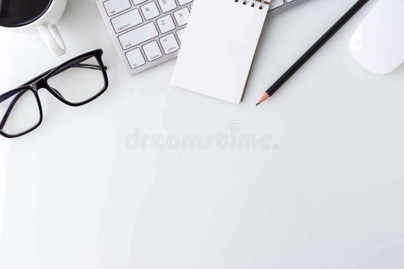 Skrivbords- tabell för modernt vitt kontor med datorbärbara datorn, noteboo royaltyfri bild
