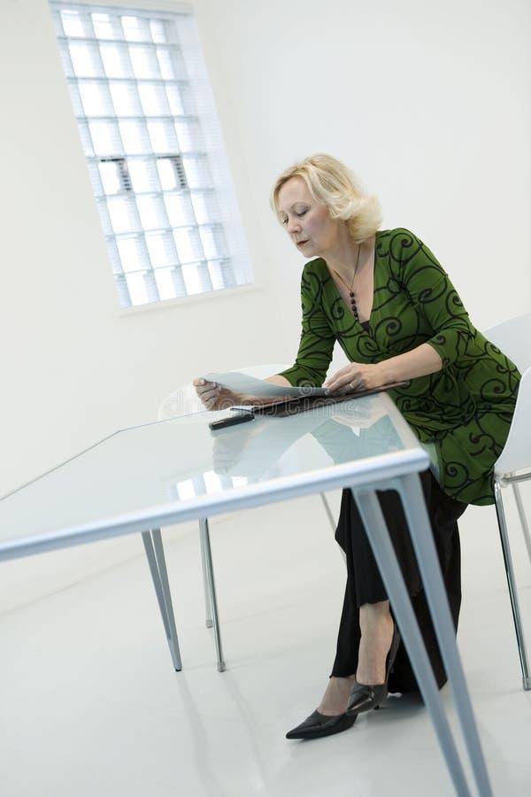 Skrivbordsarbeteavläsningskvinna Arkivfoton