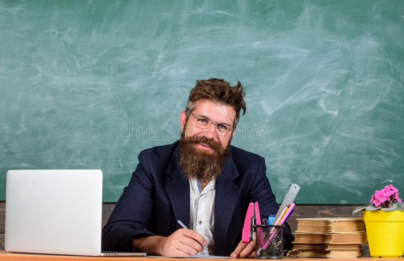 Skrivbordsarbetedel av lärareliv Skolaläraren som kontrollerar läxa- eller provläraren, sitter skrivbordet med bärbara datorn Kon royaltyfria foton