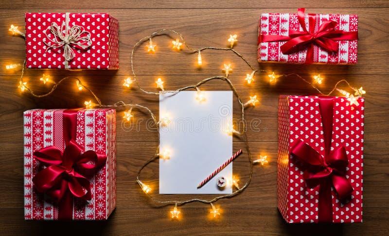 Skrivbordsikt från ovannämnt med bokstaven till santa, gåvor och julljus, retro xmas-begrepp arkivfoto