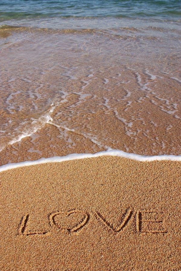 skriven strandförälskelsesand arkivbild