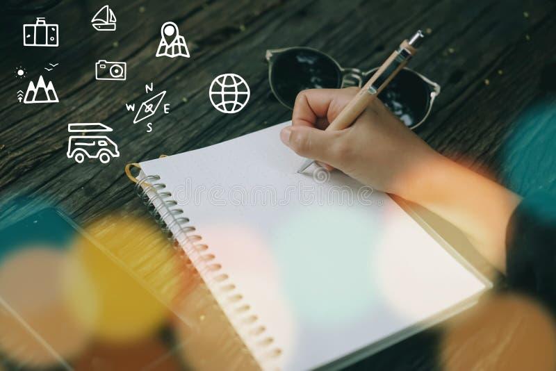 Skriver den blandade skärmen för loppsemestersymboler på kvinnahanden ner i anteckningsbok arkivbild