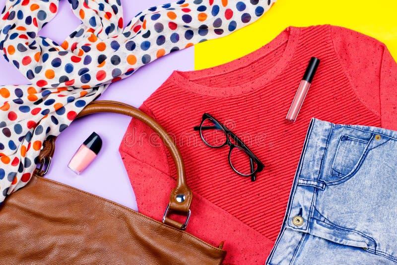 Skrivev kvinnliga kläder ut för hösten - den röda tröjan, jeans, läderhandväska, halsduken, tillbehör och sminkprodukter arkivbild