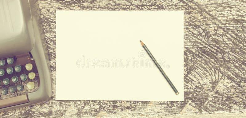 Skrivmaskin, blyertspenna och papper på det gamla sjaskiga wood skrivbordet Åtlöje upp Matte effekt för tappning arkivfoton