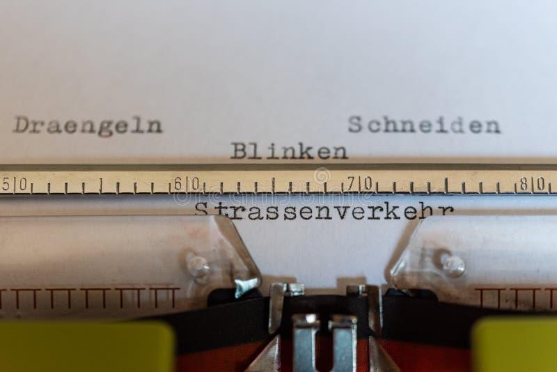 Skrivmaskin med ett blad och orden Draengeln, Schneiden, Blinken und Strassenverkehr som tömmer, klipper, exponerar och trafik royaltyfria foton